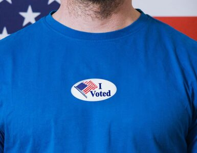 a white male with a blue shirt wears an I voted sticker with the american flag in the background