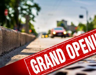 a road curbside with a sign that says Grand Opening on it