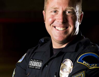 a smiling police officer with a parental advisory label on his clothing